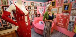 Museum guide giving a tour, standing in front of pink wall covered with black and white photos of burlesque dancers, next to mannequin wearing red burlesque dress